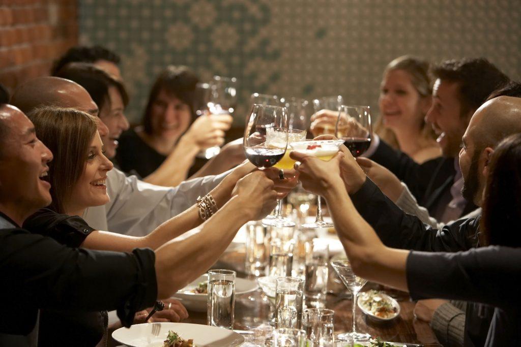 people raising glasses at restaurant